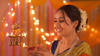Happy Indian woman lighting diyas at home with Diwali festival background - Celebration