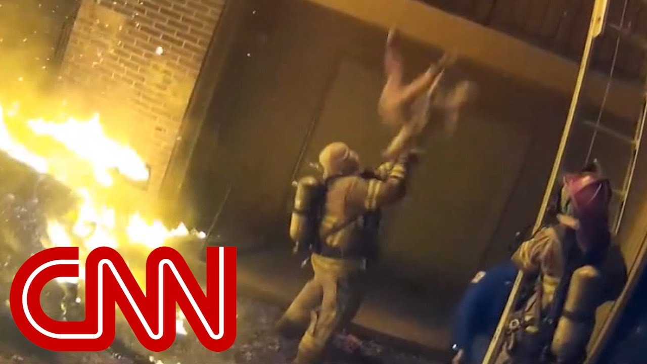 Firefighter catches child tossed from a burning building
