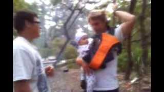 Папа сажает ребенка в рюкзак-кенгуру