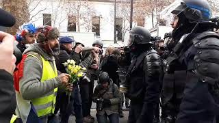 Gilets Jaunes protester offering flowers to the riot police