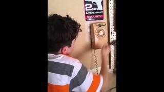 Kid tries to figure out how to use a rotary phone