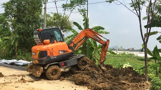 Excavator Clears Mud From The Roadside