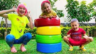 Алекс и Настя играют с красочными шинами под детскую песенку про пять цветных колес.