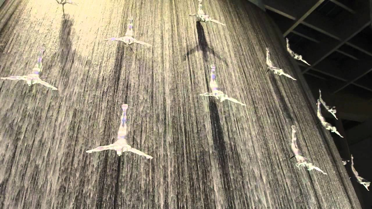 Waterfall at dubai mall with diving statues united arab