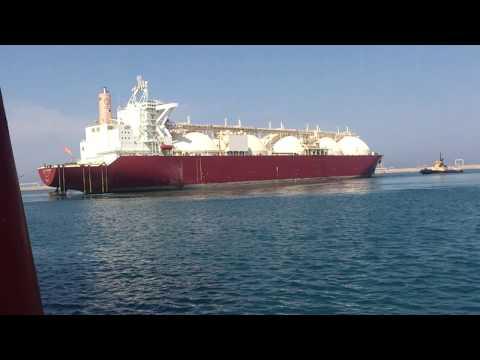 tugs playing with huge ship