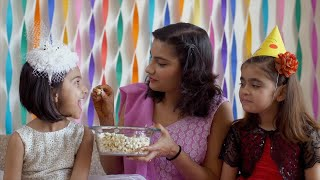 Adorable girl in white dress eating popcorn on her birthday - Family celebration at home