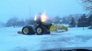 Giant John Deere Tractor Snow Plow Stuck and Spinning On the Ice.