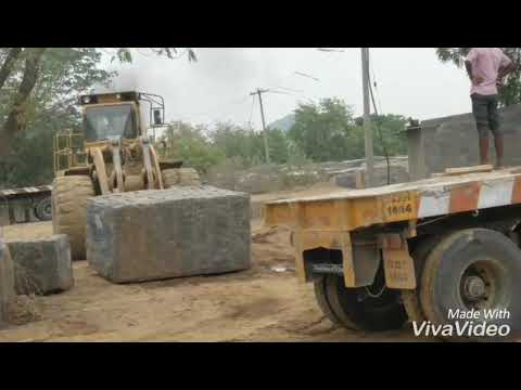 Fork lift machine at site lifting huge rocks from granite quarry