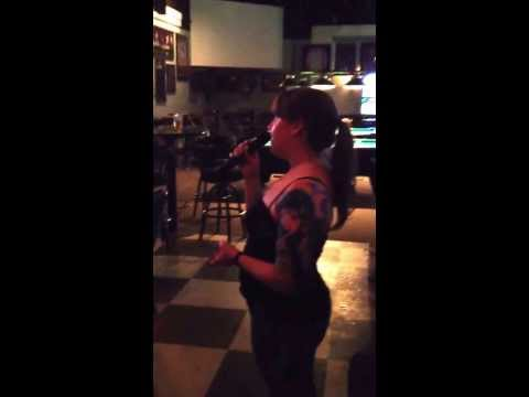 A woman in Edmonton, Alberta singing Florence + the Machine karaoke at a little hole in the wall bar