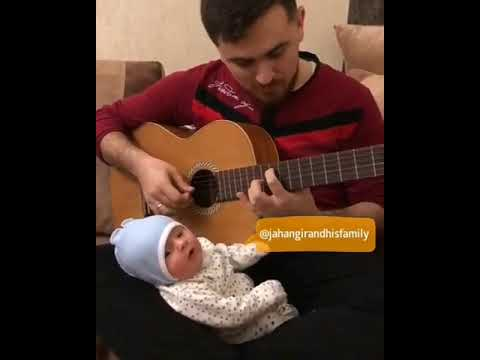 Dad Plays Guitar for Sleepy Baby - 1039407