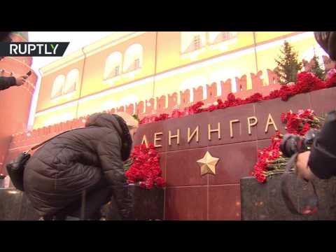 People bring candles & flowers at Leningrad Hero City monument in Moscow