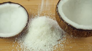A heap of shredded coconut with two halves of a healthy tropical coconut
