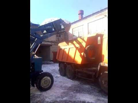 МТЗ загружает камаз снегом