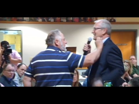 Man Stuffs Cash Into Shirt Of GOP Politician In Protest At Town Hall