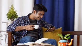 Indian man checking phone notifications with a cup of tea in his hand