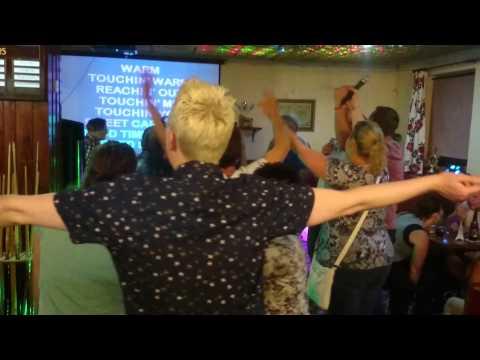 Club patrons singing  Sweet Caroline originally recorded by Neil Diamond