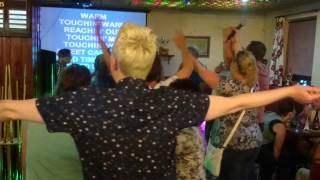Club patrons singing  Sweet Caroline originally recorded by Neil Diamond
