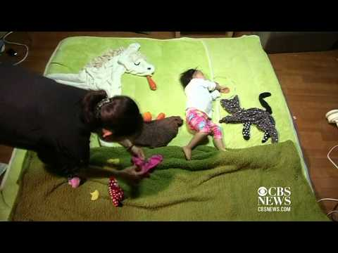 Japan mom uses sleeping baby in art project