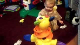 Toddler Laughing at feeding balls into giraffe toy