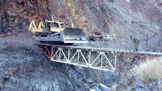 Огромный бульдозер ДЭТ 250 без водителя по краю маленького моста  который выдерживает 40 тонн.