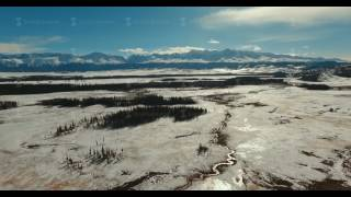 the bed of a winding mountain river in the middle of a snowy plain
