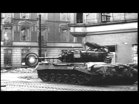 Soldiers aboard M-4 and M-26 tanks firing into buildings in Cologne, Germany. HD Stock Footage