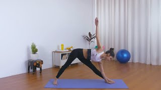 Young focused woman doing stretching exercises on a yoga mat in sportswear