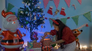 Young beautiful girl opens her gift box while sitting under a colorful Christmas tree