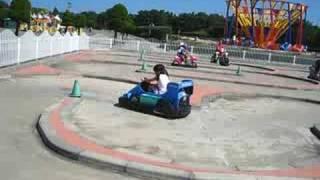 Kimmi Driving A Car At An Amusement Park