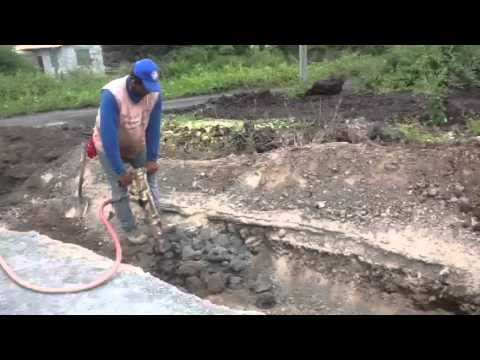Trenching for waterline in lava rock.