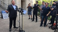 Alex Jones addresses media outside Travis County courthouse.