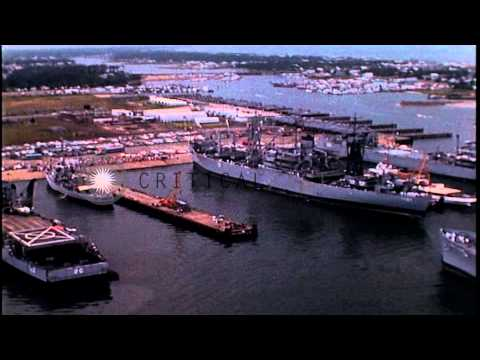 USS Liberty approaches a pier and cars at a dock along the Atlantic Ocean. HD Stock Footage