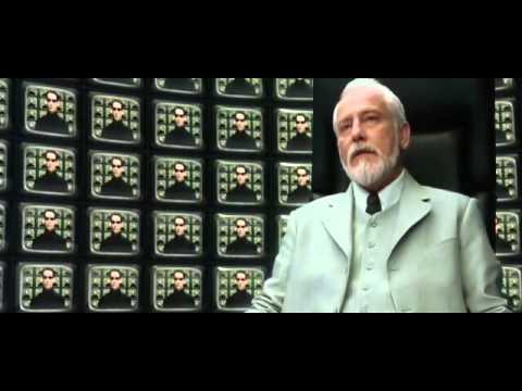 """Архитектор из """"Матрицы"""" на фоне экранов"""