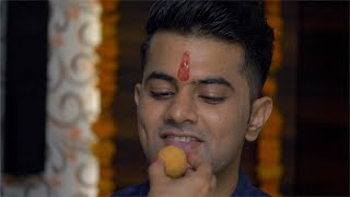 Young Indian boy eating ladoo (Indian sweet) during festival celebration