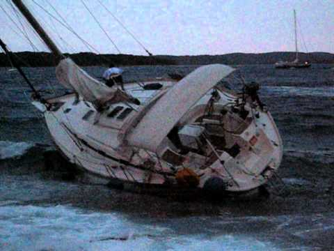 Sailboat caught in a storm crashing against the rocks ...