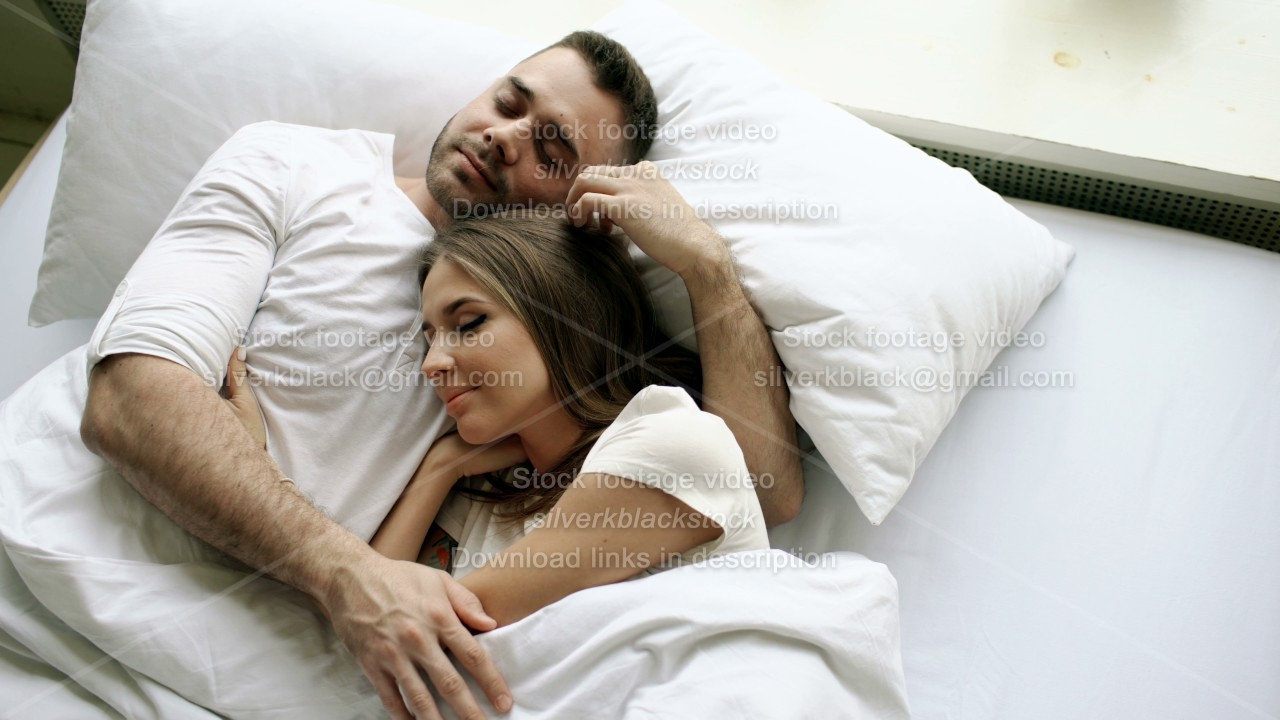 young beautiful and loving couple kiss and hug into bed while waking