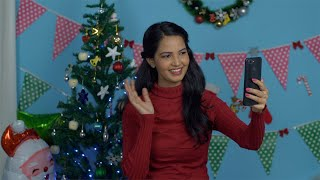 Pretty Indian girl happily greeting her friends 'Merry Christmas' on a video call