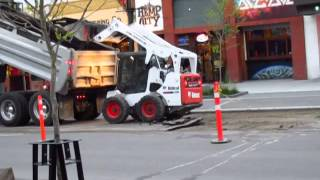 Removing asphalt from road with a bobcat - Kelowna