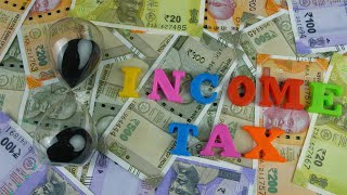 "Top view shot of colorful letters spelling the words ""Income Tax"" - finance concept"