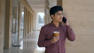 Young male employee happily receiving a call from his friend - technology concept