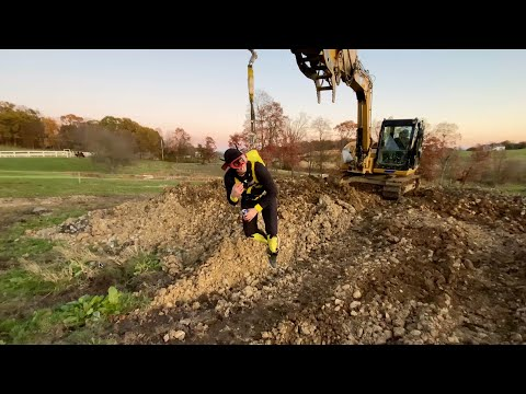Man dressed in a Batman onesie straps himself to an excavator bucket and takes flight