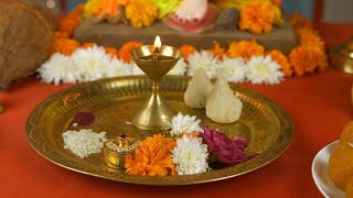 Pan shot of Lord Ganesha Idol for Ganesh Chaturthi. Flowers, Sweets, Lamp, Modak, Coconut kept in front for prayer