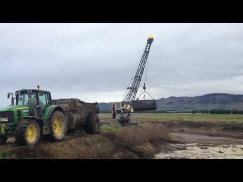 Dragline cleaning effluent pond in northern Southland NZ