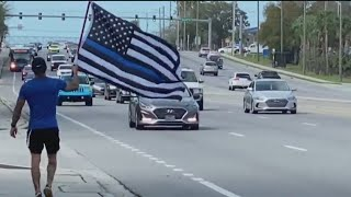 Officers in Pinellas County lined a street Thursday to salute the body of the deputy killed