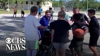 Boys help classmate in wheelchair play basketball