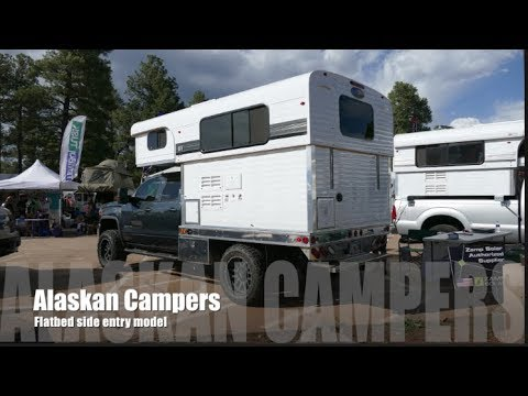 Pop up hard side camper on a flatbed with side entry by Alaskan Campers