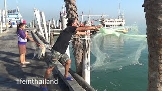 Cast net fishing off the dock in Thailand.