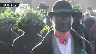 UK town residents paint their faces black celebrating Straw Bear Festival, Cambridgeshire