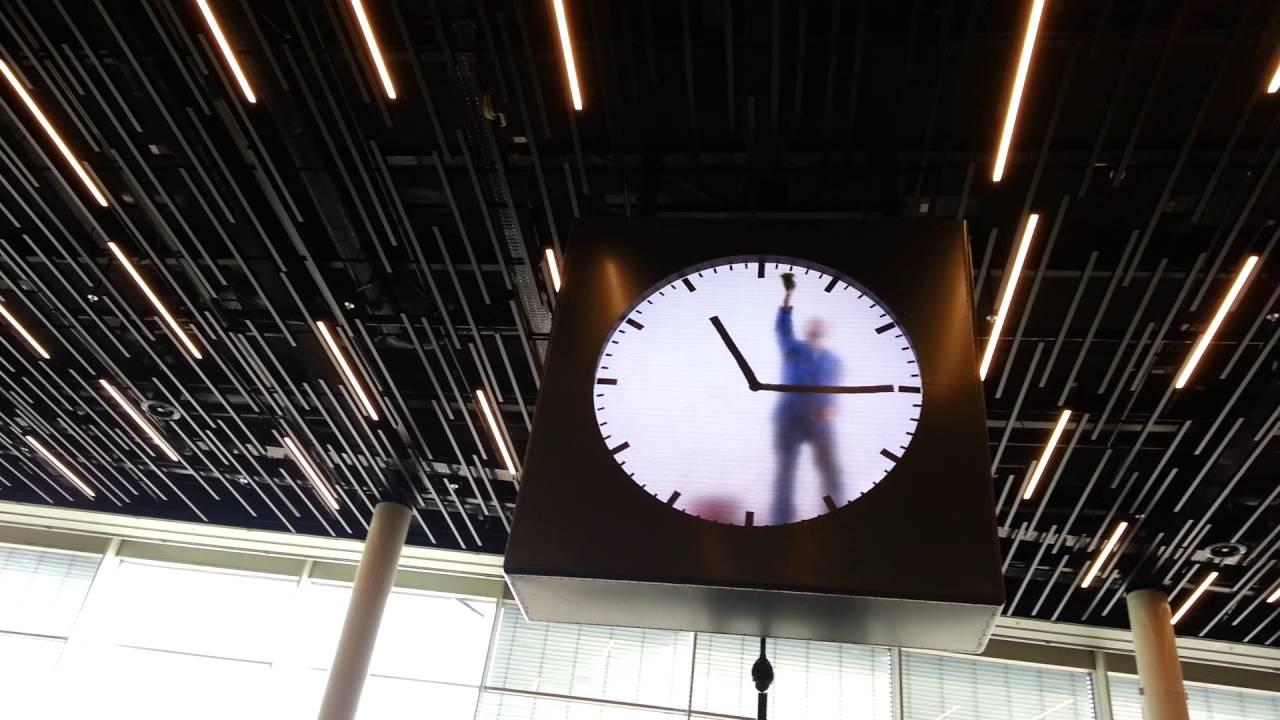 В часах амстердамского аэропорта сидит человек и рисует стрелки?
