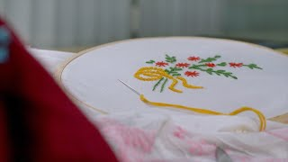Pan shot of white cloth with handmade colourful embroidery